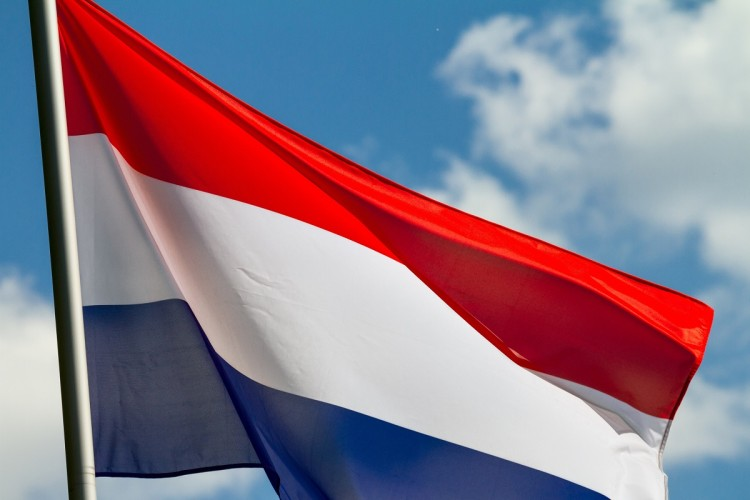 Flag of the Netherlands waving in the wind on flagpole against the sky with clouds